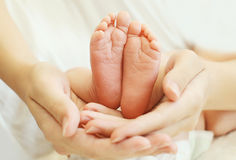 Madre que celebra en primer de los pies del bebé de las manos Imagen de archivo