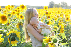 Madre que celebra a la hija del bebé en prado de la flor Foto de archivo libre de regalías
