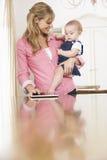 Madre que celebra a la hija del bebé mientras que usa la tableta de Digitaces Foto de archivo