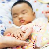 Madre que celebra la mano del bebé fotos de archivo