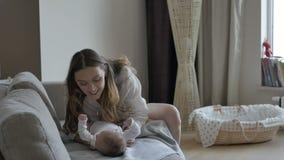Madre que celebra las piernas del ` s del bebé metrajes