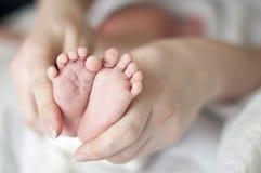 Madre que celebra pies del niño Imagenes de archivo