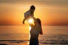 Madre que celebra a su bebé para arriba en el aire en una playa imágenes de archivo libres de regalías
