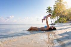 Madre que celebra a su hija del bebé en el aire en una playa tropical fotografía de archivo libre de regalías