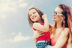 Madre que celebra a su hija en el brazo Fotos de archivo