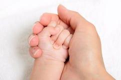 Madre que celebra una mano del bebé Foto de archivo libre de regalías