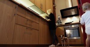 Madre que cocina cerca de sus juegos del bebé almacen de video