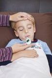 Madre que comprueba la temperatura del niño pequeño mal con el termómetro Imagenes de archivo
