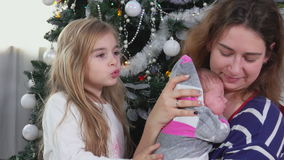 Madre que conforta al bebé cerca del árbol de navidad almacen de video