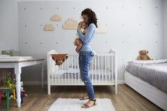 Madre que conforta al hijo recién nacido del bebé en cuarto de niños imagen de archivo