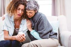 Madre que conforta a la hija tensada que se sienta en el sofá imagenes de archivo