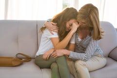Madre que conforta a su hija adolescente Imagen de archivo