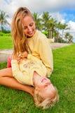 Madre que cosquillea al hijo divertido del bebé que miente en sus revestimientos Imagen de archivo