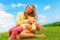 Madre que cosquillea al hijo divertido del bebé que miente en sus revestimientos Imágenes de archivo libres de regalías