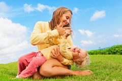 Madre que cosquillea al hijo divertido del bebé que miente en sus revestimientos imagen de archivo libre de regalías