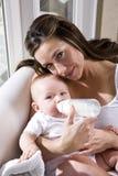 Madre que cría con biberón al viejo bebé de seis meses Foto de archivo libre de regalías