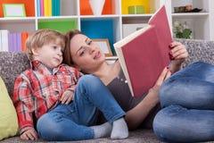 Madre que cuenta una historia al niño imagenes de archivo