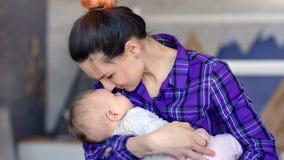Madre que cuida casual del primer medio que sonríe besando al bebé durmiente en sus manos almacen de video