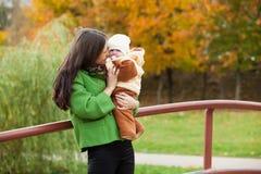 Madre que cuida con el bebé en parque Imágenes de archivo libres de regalías