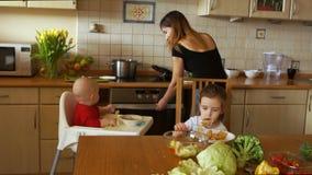 Madre que cuida hermosa en la cocina con sus dos niños - niño y muchacha preescolar Día de madres almacen de metraje de vídeo