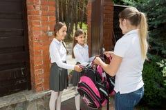 Madre que cuida joven que ve de su hija a la escuela en la mañana Imagen de archivo libre de regalías