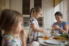 Madre que cuida joven y sus dos pequeñas hijas que comen las crepes con la miel en el desayuno en la cocina acogedora foto de archivo