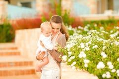 Madre que cuida que muestra las plantas a su bebé Foto de archivo libre de regalías