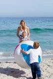 Madre que cuida y sus niños que juegan con una bola Fotografía de archivo