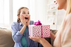 Madre que da el presente de cumpleaños a la muchacha en casa Fotos de archivo