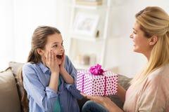 Madre que da el presente de cumpleaños a la muchacha en casa Imágenes de archivo libres de regalías