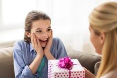 Madre que da el presente de cumpleaños a la muchacha en casa Fotos de archivo libres de regalías