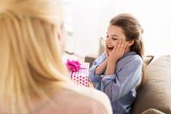 Madre que da el presente de cumpleaños a la muchacha en casa Imagenes de archivo