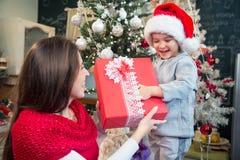 Madre que da el regalo de Navidad a su hijo Fotos de archivo