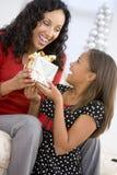 Madre que da a hija su regalo de Navidad Imagenes de archivo
