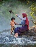 Madre que da a hija una ducha Foto de archivo libre de regalías