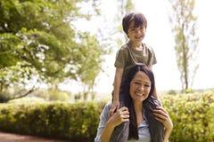 Madre que da paseo del hijo en hombros durante paseo fotografía de archivo libre de regalías