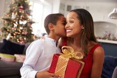 Madre que da regalos de Navidad al hijo en casa Fotos de archivo