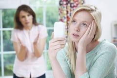 Madre que discute con la hija adolescente sobre uso del teléfono móvil Imágenes de archivo libres de regalías