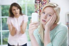 Madre que discute con la hija adolescente sobre uso del teléfono móvil Imagen de archivo