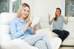Madre que discute con la hija sobre el uso de la tableta de Digitaces Imagen de archivo libre de regalías