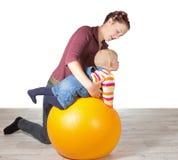 Madre que ejercita a su bebé joven Imagen de archivo