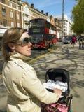 Madre que empuja el carro de bebé Imagenes de archivo