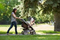 Madre que empuja el carro de bebé en el parque Imagen de archivo