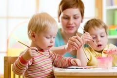 Madre que enseña a sus niños a pintar Fotos de archivo libres de regalías