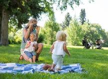 Madre que fotografía a la hija en parque Foto de archivo