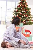 Madre que frota ligeramente al hijo durmiente en la Navidad Foto de archivo libre de regalías