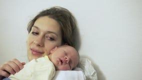Madre que frota ligeramente el hombro recién nacido del primer el dormir del bebé almacen de video