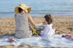 Madre que frota ligeramente a la hija en la playa Foto de archivo