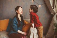 madre que habla al hijo del niño en casa Niños que comparten problemas con los padres fotos de archivo