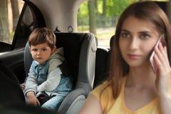 Madre que habla por el teléfono mientras que conduce el coche con su hijo en asiento trasero NI?O EN PELIGRO imagen de archivo